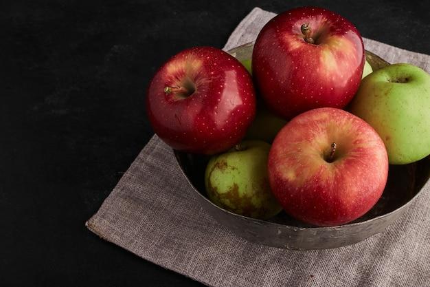 金属製のボウルに赤と緑のリンゴ、上面図。 無料写真
