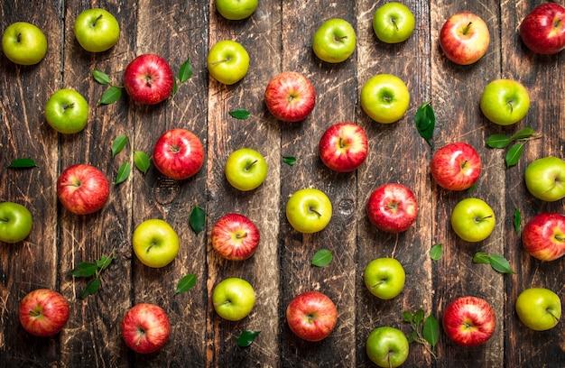 赤と緑のリンゴ。木製のテーブルの上。 Premium写真