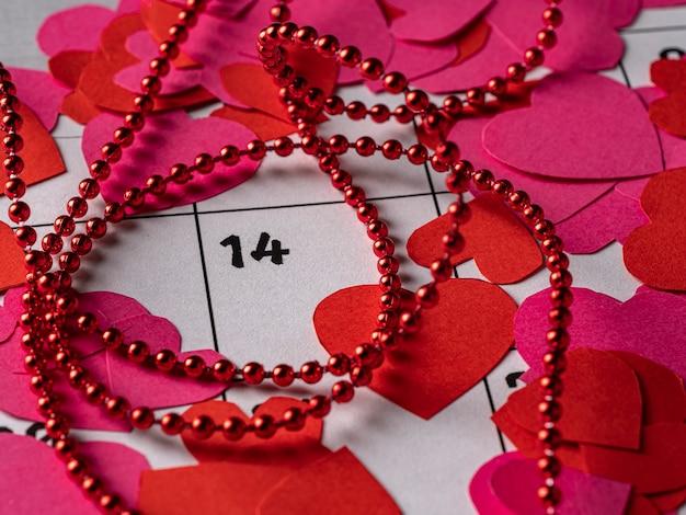 バレンタインデーと白のカレンダーに赤とピンクのハートとリボン Premium写真