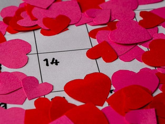 バレンタインデーと白いカレンダーの赤とピンクのハート Premium写真