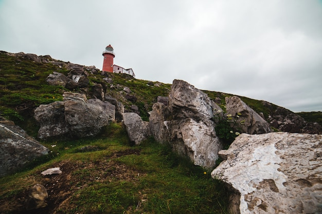 Красный и белый маяк под пасмурным небом в дневное время Бесплатные Фотографии