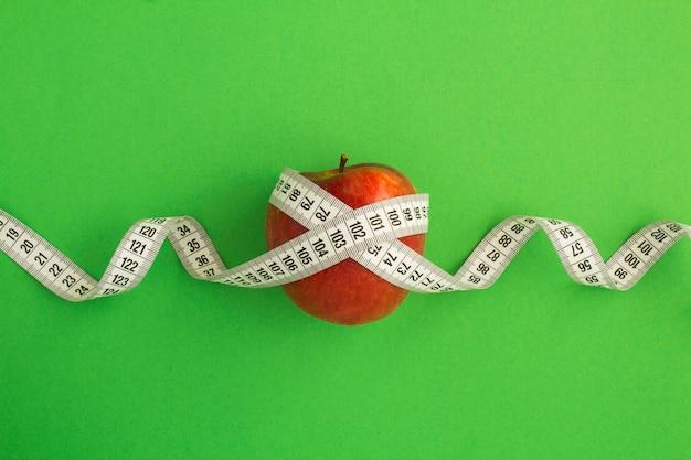 Красное яблоко и белый сантиметр на зеленом фоне Premium Фотографии