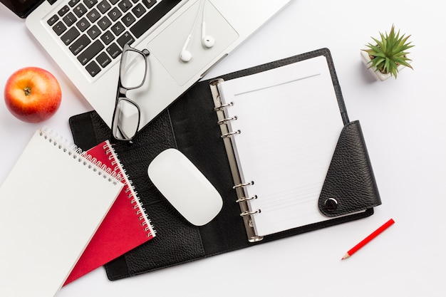Red apple,diary,mouse,eyeglasses,earphones,pencil and laptop on white desk Free Photo