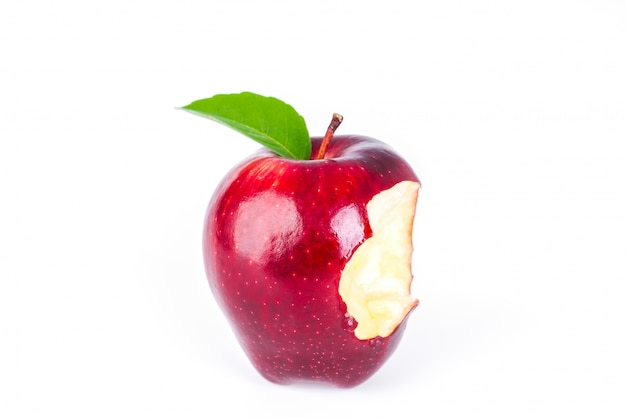 Red apple with green leaf and missing a bite . Free Photo