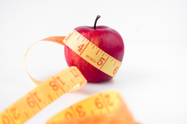 Red apple with measuring tape on table Free Photo