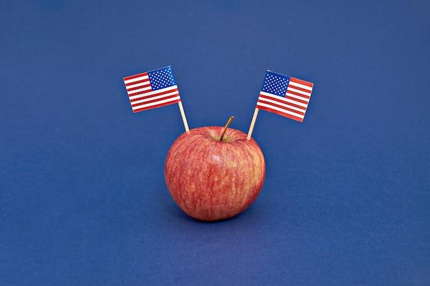 青の背景にアメリカの2つのフラグと赤いリンゴ。アメリカ大統領の日コンセプト Premium写真