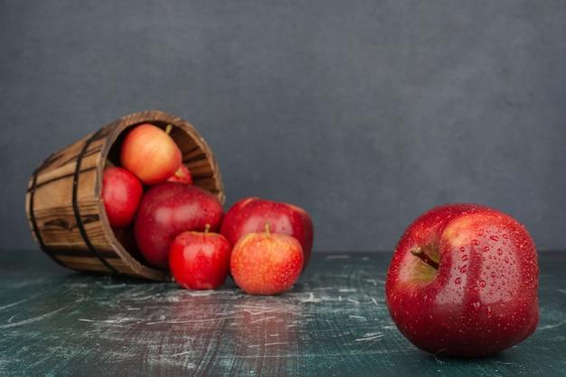 Красные яблоки падают из ведра на мраморный стол. Бесплатные Фотографии
