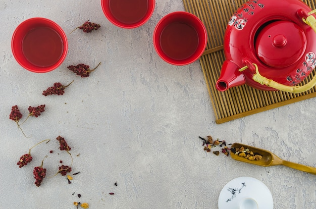Red asian cup and teapot with herbs on textured grey background Free Photo