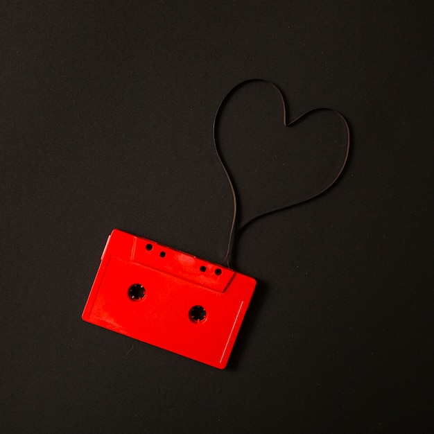 Red audio cassette with magnetic tape in shape of heart on black ...