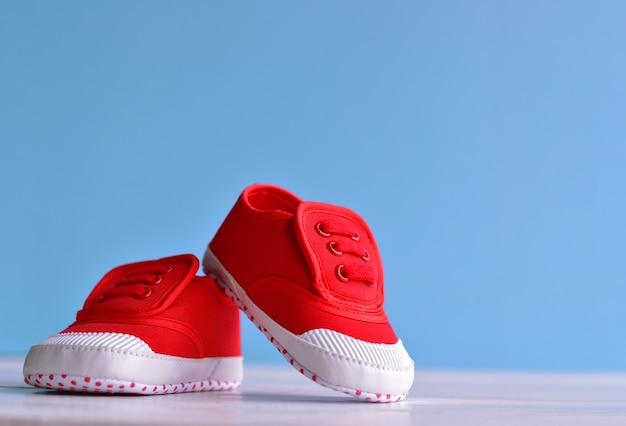 Red baby boy shoes on white wooden floor and blue background Premium Photo