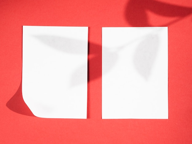 Red background with a leaf branch shadow on two white blankets Free Photo