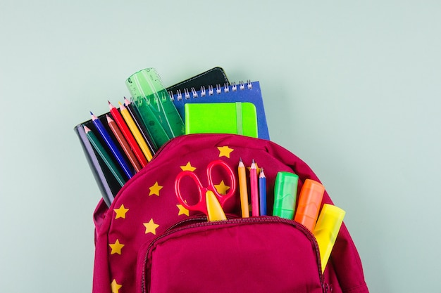 Red backpack with different colorful stationery on pastel green Premium Photo