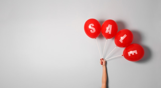Red balloons with sign sale in woman hand with copy space for your text Premium Photo
