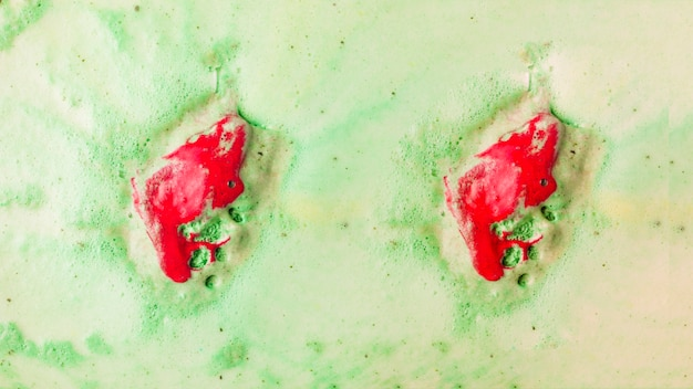 Red bathbomb dissolve in green bubble bath water Free Photo