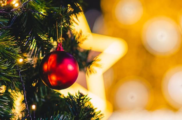 Красная безделушка висит на елке с красочным фоном Premium Фотографии
