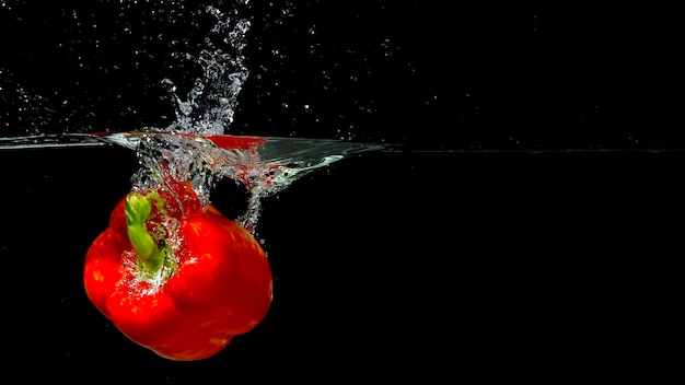 Red bell pepper splashing into water over black background Free Photo