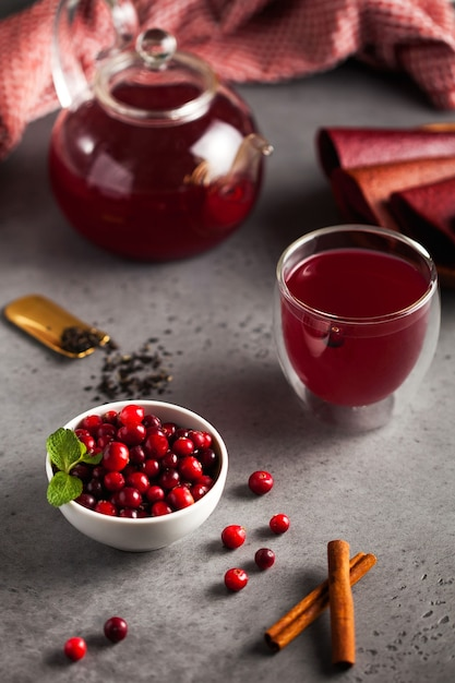 Red berry tea of their cranberries, black tea, cinnamon, ginger and mint in a teapot with a mug and bowl of cranberries Premium Photo