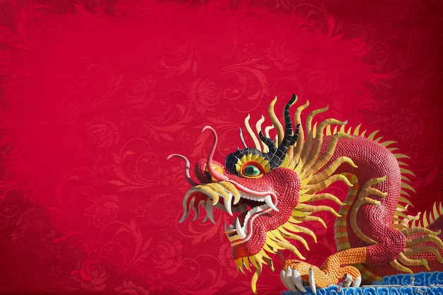 Red big dragon statue on red texture background . Premium Photo