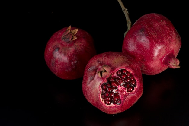Red big pomegranates on black, top view Free Photo