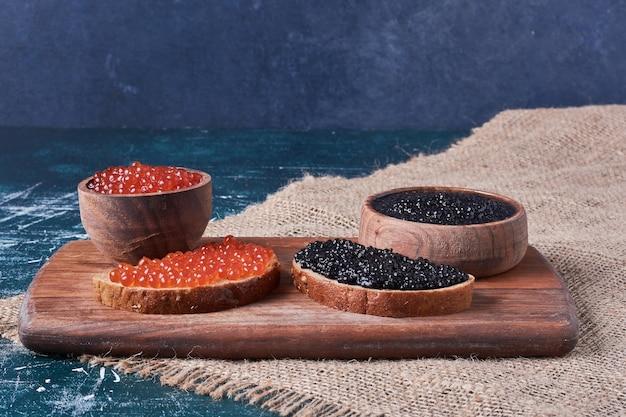Caviale rosso e nero su tavola di legno. Foto Gratuite