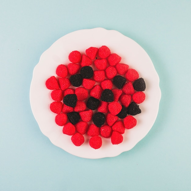 Red and black cranberry candies on plate Free Photo