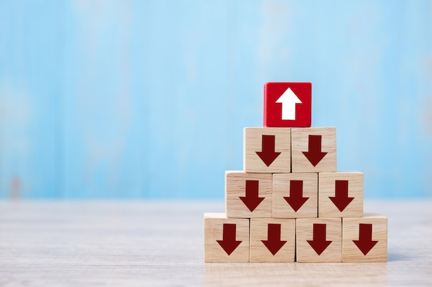 Red block with different direction of arrow on table background. Premium Photo