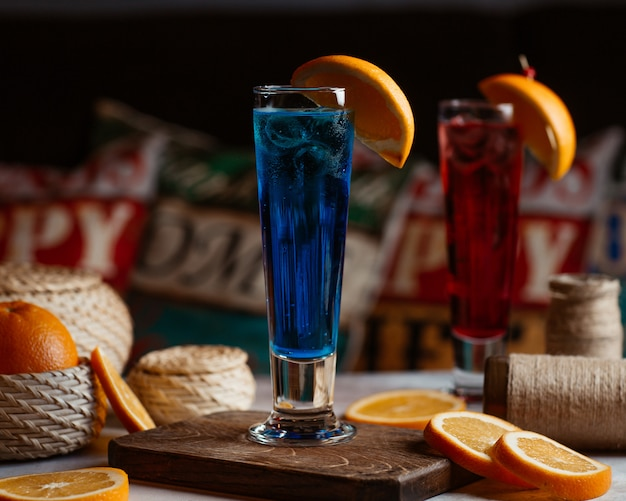 Red and blue cocktails with orange slices on the top Free Photo