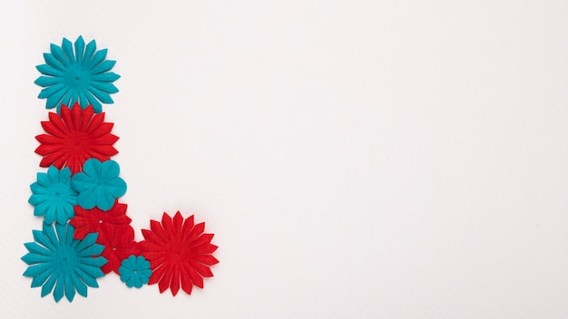 Red and blue flower on the corner of white backdrop Free Photo