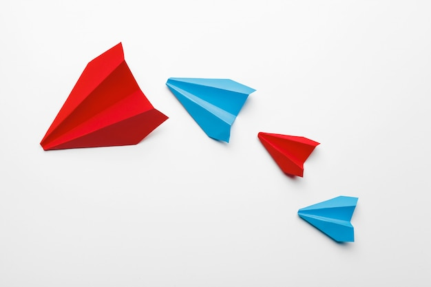 Red and blue paper planes on white background Premium Photo
