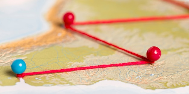 Red and blue pushpins with thread on route map Free Photo