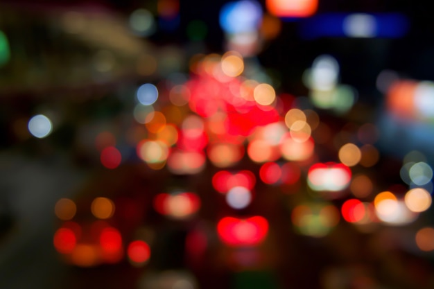 Red bokeh light from car on road in the city at night time. defocused of night traffic. Premium Photo
