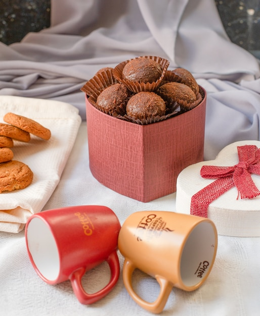 A red box of chocolate pralines with empty coffee cups on the table. Free Photo