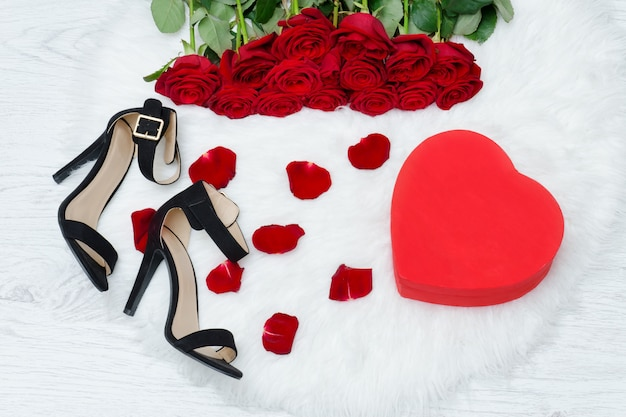 Red boxes in heart shape, black shoes and a bouquet of red roses on a white fur Premium Photo