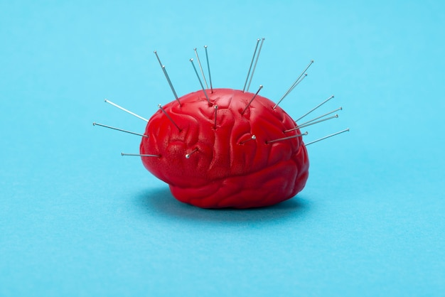 Red brain on a blue background with injected needles. Premium Photo