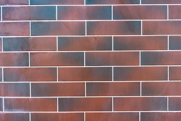 赤レンガの壁。白い詰物が付いている暗い茶色と赤レンガのテクスチャ 無料写真