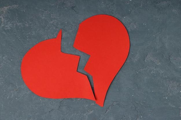 Red broken heart on concrete Premium Photo