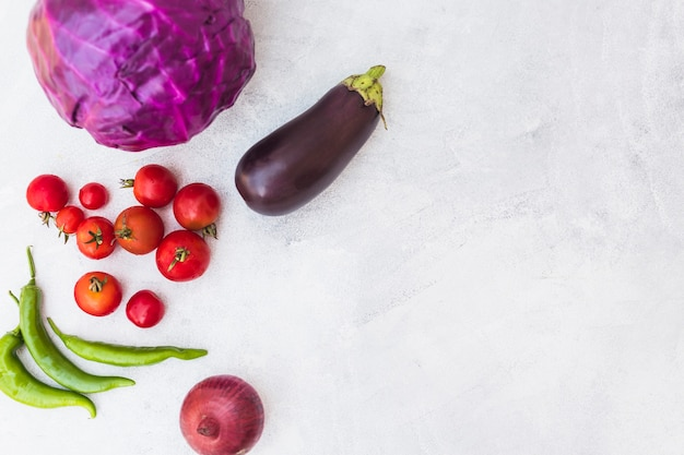 Red cabbage; tomatoes; green chilies; onion and eggplant on white textured background Free Photo