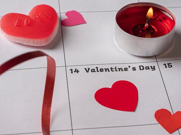 バレンタインデーと白いカレンダーの赤いキャンドルハートとリボン Premium写真