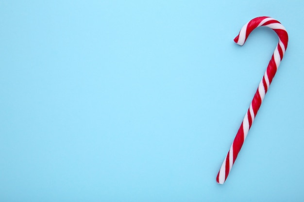 Red candy canes on a blue background, sweets Premium Photo