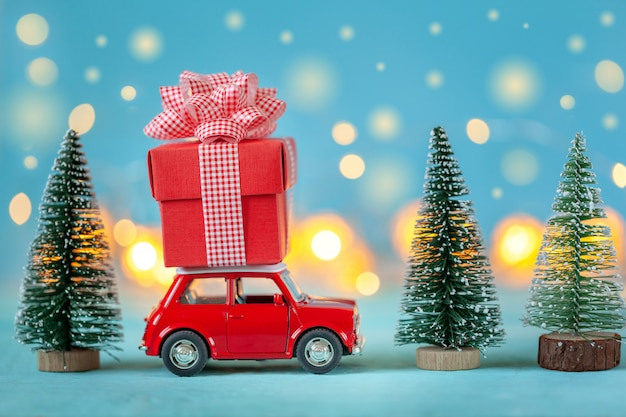 Red car carrying on roof a gift box  and christmas tree. christmas and new year concept Premium Photo