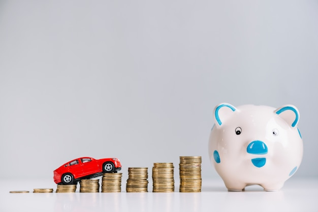 Red car driving over increasing stacked coins near piggybank Free Photo