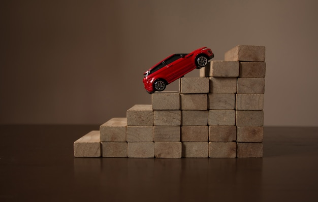 Red car going up on roll stair step of wooden staircase stack, natural bright light background Premium Photo