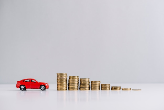 Red car near decreasing stacked coins Free Photo