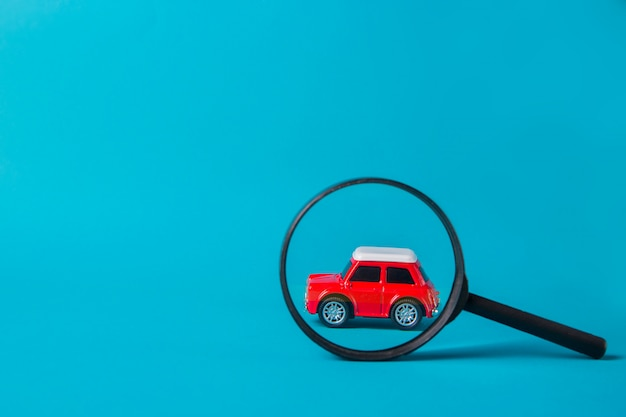 Red car peeked out with a magnifying glass on blue background. technical inspection and machine search Premium Photo
