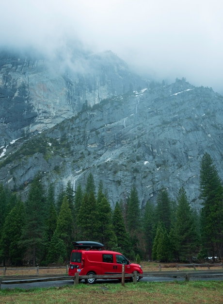 Red car of traveller  parked in yosemite national park with beauty cliff background. Premium Photo