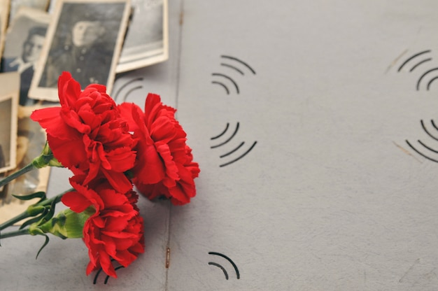 Red carnations on the background of an old photo album with military photos. day of memory and military glory. Premium Photo