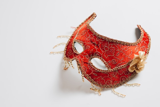 Red carnival mask on light table Free Photo