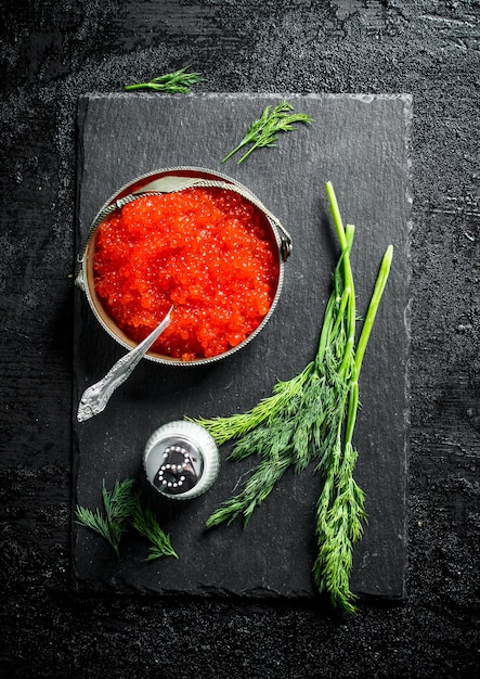 Red caviar in a bowl on a black stone board with salt and dill. on black rustic Premium Photo