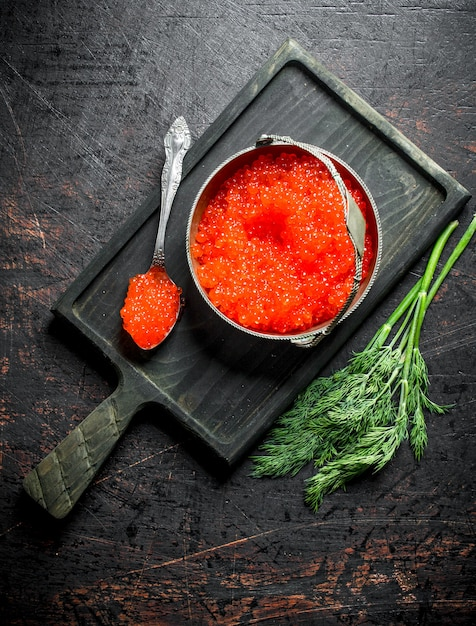 Red caviar in a bowl and a spoon on a cutting board with dill. on dark rustic Premium Photo