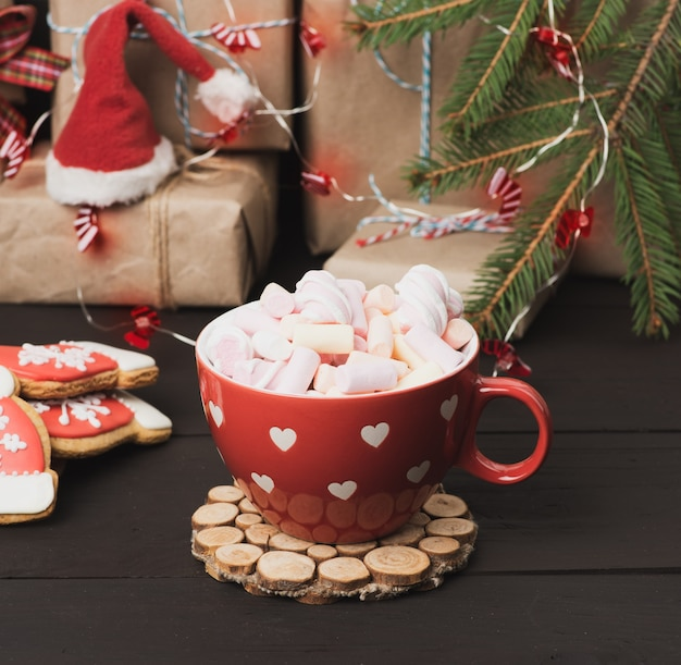 Красная керамическая чашка с какао и зефиром, за подарочной коробкой и елочной игрушкой Premium Фотографии